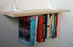 Some elastic, a board, brackets and a stapler are the essential elements to this remarkably simple DIY bookshelf project. In short: this is made of stuff that many of us already have on hand or can purchase inexpensively at any hardware store.