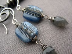 These earrings feature shimmering, deep blue kyanite squares that I have intricately wrapped and paired with unique carved gray moonstone drops. By Brenda McGowan