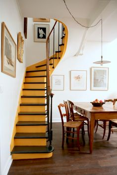 A warm punch of yellow on the stairs highlight its luscious curves and brings a vibrancy to the muted tones of the apartment. In addition, four of the six dining chairs were sourced from the Paris fleas to complement the existing ones. All photos by: Niya Bascom Photography
