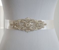 This beautiful vintage inspired bridal sash is embellished with high quality rhinestone crystal and pearls. Sparkles beautifully. The embellishment is 2.5 wide x 6 long. The sash is made with double faced satin ribbon 1.5 wide and is 3 yards long. Perfect for your special day. PROCESSING: Please allow 3-5 business days for production. Also be sure to leave the date you require your order or your wedding date. For rush order, please convo us before placing your order.  SHIPPING: Order will be…