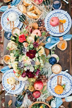 A decadent Thanksgiving spread with vibrant flowers and adorable place settings.