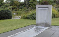 Welch ein Kontrastprogramm. Im Hintergrund: Ein Teich in wilder Natürlichkeit, eingerahmt von gezähmter Natur. Im Vordergrund: Ein Wasserspiel, das aus einem formschönen Brunnen mit klaren Linien in gerade Bahnen fließt.