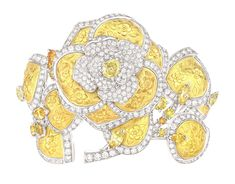 The exquisite Chanel Camélia Solaire bracelet layers the warmest yellow gold leaves under a white diamond flower, interspersed with gleaming yellow diamonds, resulting in a piece that almost glows