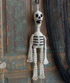 spooky Halloween crochet pattern is perfect for hanging on your door to greet trick-or-treaters or displaying inside your home to spread some ghoulish charm. The black and white skeleton adds
