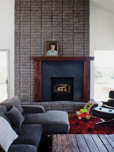 A reclaimed walnut mantel surrounds honed granite for this one-of-a-kind fireplace. Art is placed off-center to add to the asymmetric quality. Only on HGTV.com.