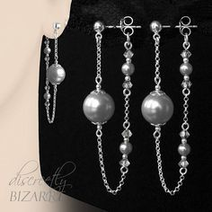 Design The earrings hang from the front to the back of the ear lobe which creates an unusual & attractive 3D effect. A thin silver chain attached to a plain ear stud drapes under the ear to connect with the rear scroll fitting. A large pearl bead hangs at the front, the back has two