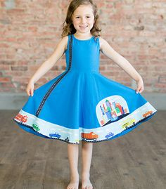 The new Busy Dresses from Princess Awesome are perfect for girls who dresses AND cars, trucks, trains, and planes. This Cars Busy Dress features a road and cars stitched onto a soft, stretchy dress, with custom-designed vehicles on the ends of the sashes allowing the little girl wearing the dress to drive them on the road and around town. Hidden side pockets allow for storage of extra cars, acorns, pebbles, and other treasures. Sizes 18mo-6y.