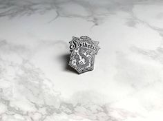 ★ Soft enamel ★ Harry Potter ★ White with silver ★ Silver clutch ★ Size is 3 cm All of our products are shipped by regular mail. All of the orders will be shipped in a cute air cushion enveloppe and should fit through the mailbox. The shipment wont be tracked because we want to keep