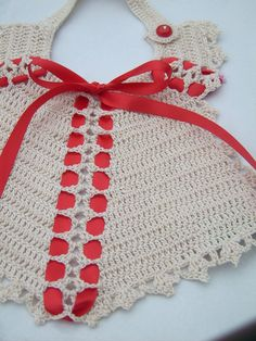 Antiquities are over 100 years old to be considered antiques, but this is a newly made bib that is created from a vintage pattern is yet to have the old look. Ribbons and lace features double crochet stitches and shells inside the body of the bib. There is a shell and picot border and a nice neck strap that fastens with a Cherry Red button on the shoulder.
