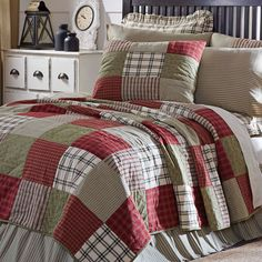 Traditional block patchwork is updated in this country-casual quilt. Featuring hand-quilting on various brick red, sage, and khaki block layout in plaid, striped, and ditsy fabrics #countrybedroom #bedroomdecorideas