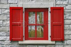 Red Window shutters, grey stone wall
