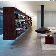 Para separar o living do corredor de entrada, o arquiteto Isay Weinfeld criou uma longa estante vazada de madeira que fica suspensa do piso por tubos de aço fixados no teto.