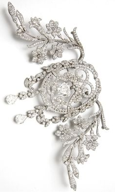 A  BELLE ÉPOQUE DIAMOND CORSAGE ORNAMENT, BY CHAUMET.  The central heart-shaped diamond weighing 5.48 carats suspended within a twin 'L' monogram mounted with old-cut diamonds to the collet border and wreath surround suspending two pear-shaped diamonds, with pavé-set diamond floral spray sides, converts to form three brooches, adapted, circa 1905.