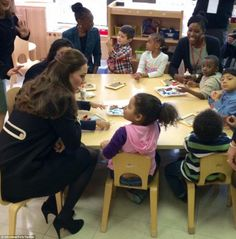 Meeting the kids: Kate leans in close to listen to a young girl at the Northside center. S...