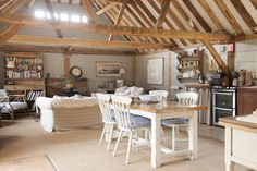 The living, kitchen and dining room is all open-plan, lined with pale blue-painted boards and honey beams