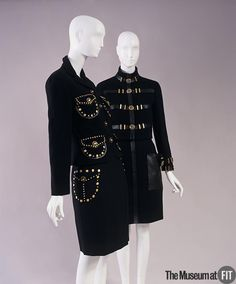 Suits | Designer: Gianni Versace (Italian, 1946-1997) | Italy, 1992 | Black wool and leather | Versace adorned this suit shown on the right with metallic buttons that display his company's distinctive logo. It features the head of Medusa – a woman from ancient Greek mythology who was transformed into a monster as punishment for her seductive and lustful actions. This made her the ideal heroine for Versace's unique brand of sexually expressive clothing | The Museum at FIT
