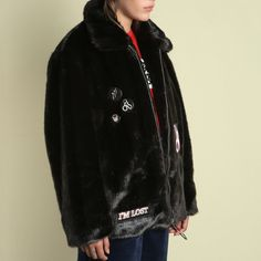 The Hyein Seo Cropped Faux Fur Jacket is a dark brown faux fur coat. Made of acrylic it features short hair mink faux fur with patch and badge details.