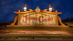 """A wooden engraving that says """"Jungle Cruise"""" on top of a building"""