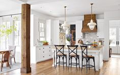 The Crouches utilized reclaimed materials to give the kitchen a lived-in feel. Take, for example, the spacious island supported by antique porch posts or the range hood crafted from salvaged pine.