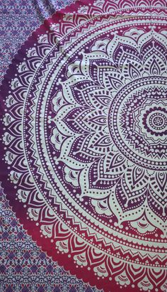 A rectangular mandala tapestry comprising of floral inspired patterns in a striking ombre of shades of purple and pink.