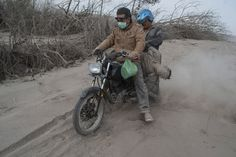 The ash-covered body of a victim is collected by two men on a motorbike following an eruption of the 2,460-metre volcano