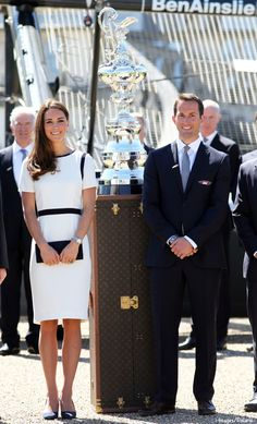 Catherine, Duchess of Cambridge, aka Kate Middleton, with Sir Ben Ainslie next to the America's Cup while visiting the National Maritime Museum. Kate is wearing Jaeger's 'Crepe Dress with Trim,' Stuart Weitzman Muse clutch, the Asprey Woodland Collection charms necklace, and her blue suede heels from Alexander McQueen. 6/10/14