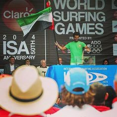 Mohammed Rahma holding up the UAE flag at the ISA World Surfing Championship in Peru.  He is the first Emirati surfer to participate in this competition.