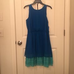 Jessica Simpson Dress NWT Never worn Jessica Simpson dress. Beautiful blue color, lining is also blue with Aqua/teal Ruffles at the bottom. No zipper, single button on the back. Comes with original nude colored belt purchased with dress. Never worn, size L. Additional pictures or info upon request. Jessica Simpson Dresses Midi