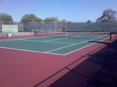 Green tennis court with a burgundy surround.