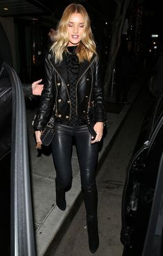Rosie Huntington-Whiteley wears a velvet top, Balmain jacket, leather leggings, and boots