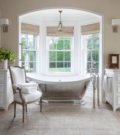 Elegant spa-like bathroom boasts an arched nook fitted with bay windows dressed in bamboo roman shades lit by a small crystal chandelier hung over a cast iron freestanding tub paired with a floor mounted tub filler fixed in front of a pink and taupe bath rug placed under a white French chair.