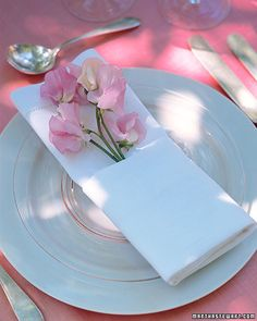 DIY Weddings | Martha Stewart Weddings  Go to External Site  »  Napkin with Flowers    Weddings are full of flowers, but sometimes the littlest arrangements make the biggest impact: Guests will be delighted to find cut flowers tucked into their napkins. To keep the blooms from wilting during the cocktail hour, slip the stems into little vials of water (available at floral shops). To fold the napkin, lay it on a flat surface, and fold in half widthwise so the f...