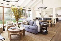 A bright and spacious living room with light blye sofa, wood coffee table, and branches as décor