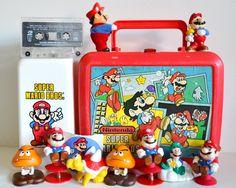 Vintage Super Mario Bros Lot. Lunchbox, Figures, Cup Dispenser, Cassette Tape, Sticker. Instant Collection Original 80s Nintendo Collectible. $85.95, via Etsy.