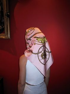Pink Hermes head scarf, tied under chin