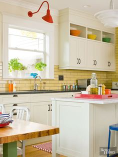 Colorful ceramic tiles make standout companions for white cabinets. Simply-lined yellow subway tiles suit this kitchen's vintage vibe, make a high-contrast partner for the cabinets, and complement the retro scheme. Gray grout lines bring a touch of depth to the sunshine-bright backsplash.