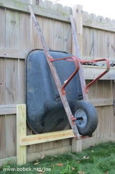 This is right up my alley since I'm not keen on taking up storage space in my garage. A few short 2x4's, screws, and some clothes line is all you need to get your wheelbarrow up off the ground and stored along a fence or outside garage wall to create your own holder. This is especially handy to keep from having to move the wheelbarrow every time you need access to the area.