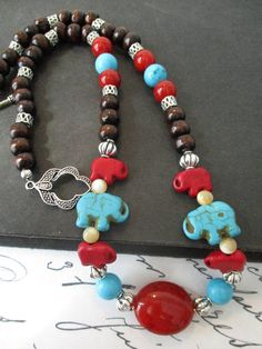 Handcrafted, one of a kind, tribal inspired beaded necklace featuring red and turquoise howlite elephants, glossy dark stained wood, mother of pearl, turqupise, Tibetan silver metalwork, and acrylic bead accents.