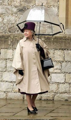 Queen Elizabeth II in casual clothes and a brolly!