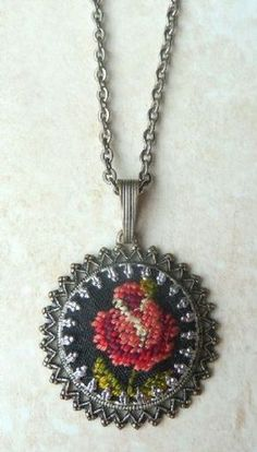 A vintage, hand crafted petit point, embroidered pendant and Necklace.  The pendant features a lovely hand embroidered rose on a black background