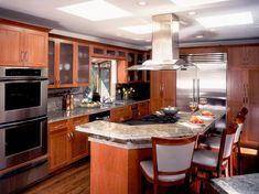 Wood cabinets create a polished frame for this kitchen design. A curved island with neutral granite countertop adds nice shape against the sharp lines of the cabinetry and creates an eat in space. Gray leather cushion upholstery on the wood bar chairs pulls from the cool tones in the countertop. A stainless steel range adds a modern finish over the stovetop.