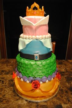Disney princess cake, featuring sleeping beauty, cinderella, ariel and belle. I love how ariel is represented by green scales.