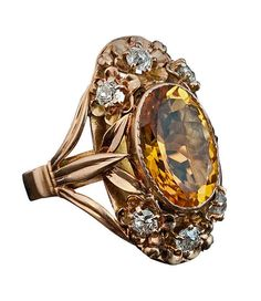 Art Nouveau Citrine, Diamond and Gold Ring, circa 1910  A 14K rose gold ring of an openwork floral design is bezel set with an oval citrin (14.5 x 10 x 6.5 mm, approximately 5 carats) vertically flanked by six gold flowers each prong-set with an old cut diamond (estimated combined diamond weight 0.80 ct).  The ring is marked with later Russian control stamps from the 1930s.