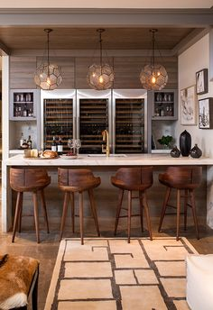 I love this bar and wine storage set up. Three Arteriors Beck Pendants illuminating a marble waterfall bar fitted with a wet bar sink and gold gooseneck faucet lined with wood counter stools. Basement Bar Designs, Home Bar Designs, Basement Ideas, Wet Bar Designs, Rustic Basement, Cozy Basement, Walkout Basement, Modern Basement, Small Basement Bars