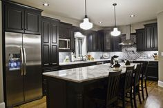 Love the contrast between the black cabinets and the light countertop done by Designer Emily