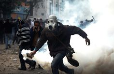 A masked protester throws a gas canister towards Egyptian riot police