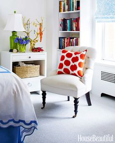 A Madeline Weinrib pillow adds a splash of orange to the Gloria chair by Mitchell Gold + Bob Williams.