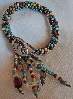 Picasso Kumihimo bracelet with a Kokopelli button by carricole, $50.00