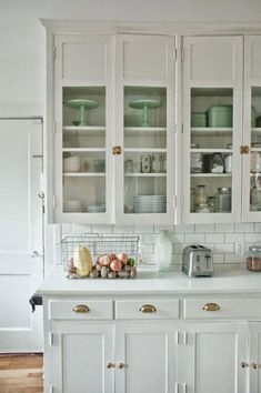 this white kitchen with vintage brass hardware is beautiful