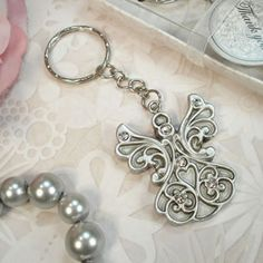 Antique Silver Design Angel Keychain - Leave your guests in awe with our wonderfully handcrafted angel keychain favor. Crafted in antique silver polyresin with rhinestone accents, this favor not only has beauty but usefullness as well.  http://www.favorfavorbaby.com/p-DL4322.htm